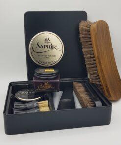 Onze Saphir schoenpoetsset waarbij de uitpoetsborstel tegen de zijkant van de doos rust en de Mirror Gloss op de Pommadier is geplaatst