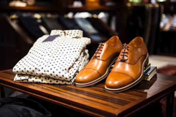 Mooie cognac kleurige nette leren schoenen naast een wit overhemd met blauw patroon