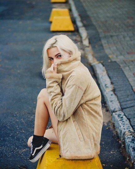 Dame met een beige jas aan die op een straat zit met zwarte sneakers