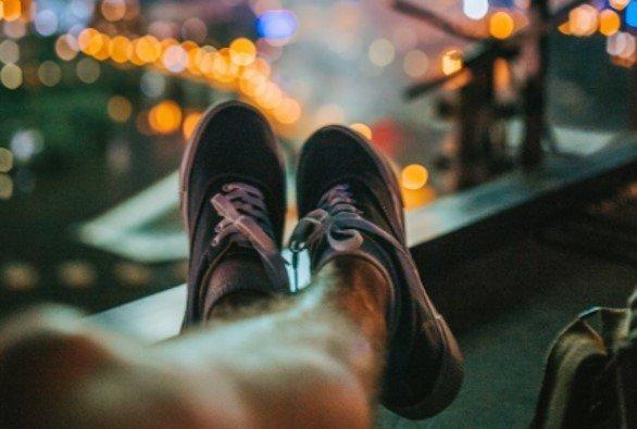 Twee benen die over elkaar geslagen zijn met grijze sneakers