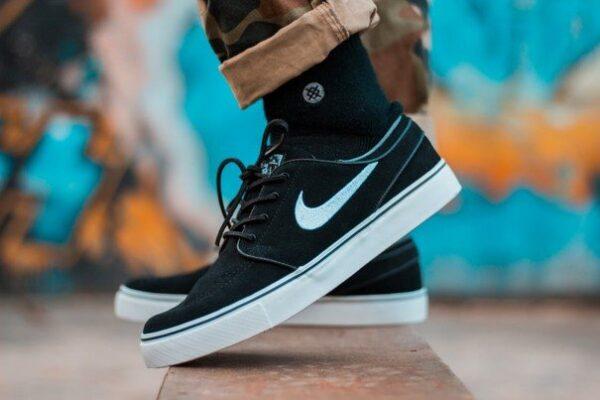 Twee zwarte Nike sneakers van dichtbij gefotografeerd met een blauwe graffiti achtergrond