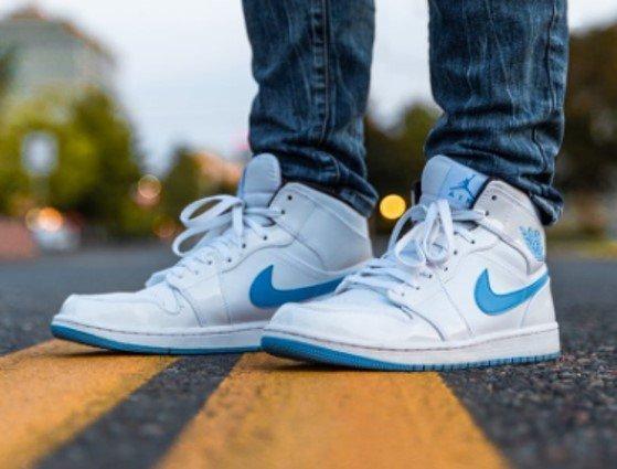 Witte nike sneakers met blauwe accenten op een weg met een gele doorgetrokken streep