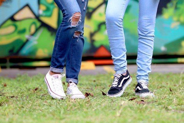 vier benen met 2 paar sneakers staande op een grasveld